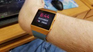 Persona lleva un dispositivo wearable mostrando la hora y medidas fisiológicas